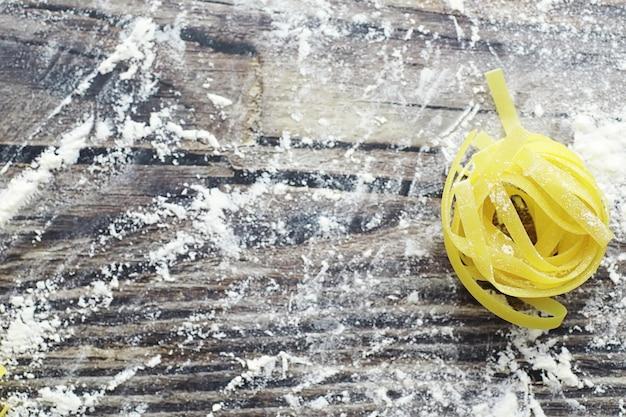 Pasta cruda sul tavolo. tagliatelle sotto forma di nidi. farina e condimenti.