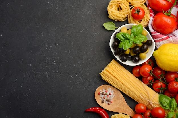 Pasta, verdure, erbe e spezie per cibo italiano su sfondo nero