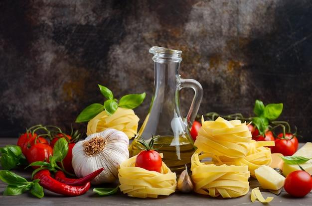 Pasta, verdure, erbe e spezie per cibo italiano sullo sfondo in legno.