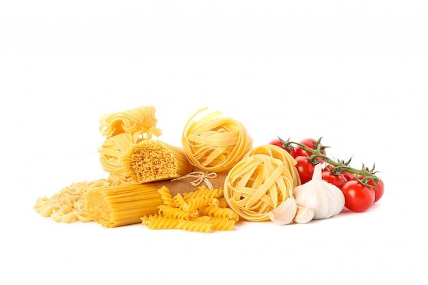 Pasta e verdure isolate su bianco. pasta integrale non cotta