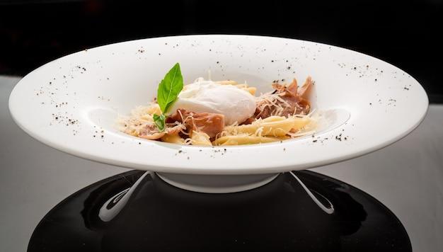 Pasta con pancetta e uovo in camicia sopra. fuoco selettivo sull'uovo di poach.