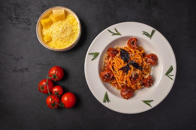 Pasta con pomodori al forno, parmigiano grattugiato e pesto in ciotole di ceramica su sfondo scuro di grafite, vista dall'alto, spazio di copia
