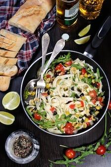 Pasta con olive schiacciate e pomodorini, rucola.