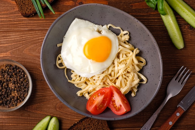Pasta con uova, pomodori ed erbe su uno sfondo di legno