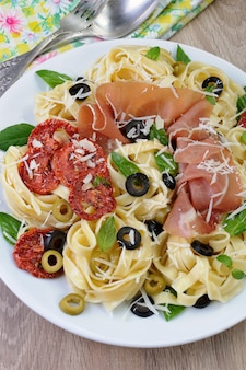 Pasta con prosciutto cotto, olive, pomodori secchi e parmigiano