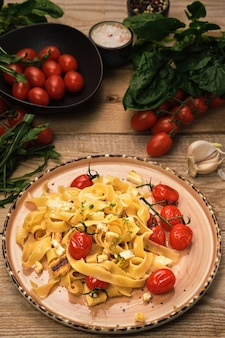 Pasta con fette di formaggio grigliate, pomodorini fritti e olio di oliva