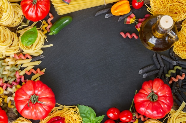 Pasta con ingridients come cornice con copia spazio su pietra nera