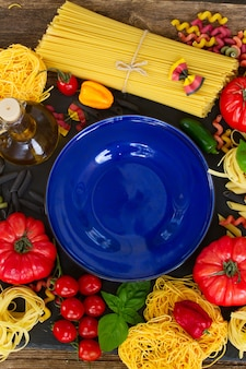 Pasta con ingridients e piatto blu vuoto