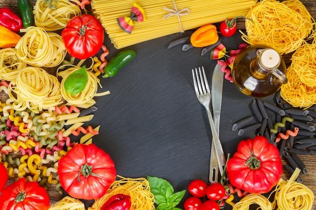 Pasta con ingridients con forchetta e coltello, copia spazio sulla lavagna