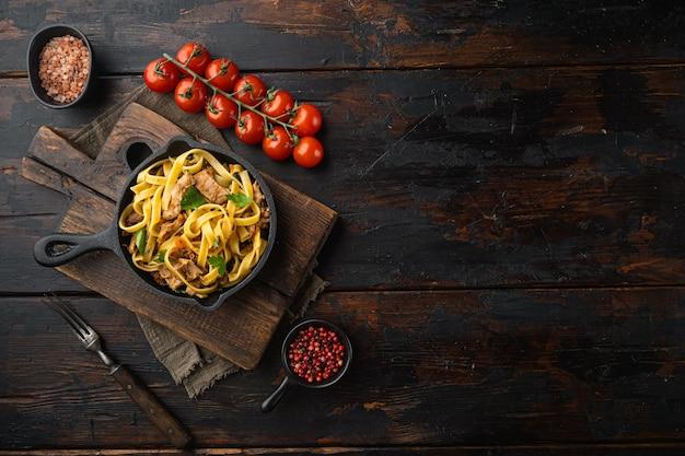 Pasta con rosmarino stufato di coniglio set, in padella in ghisa o pentola, sul vecchio tavolo in legno scuro, vista dall'alto laici piatta