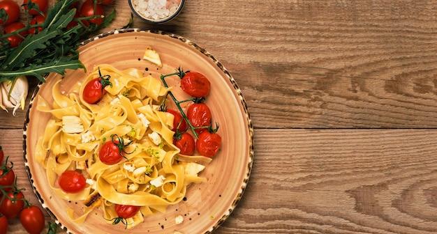 Pasta con fette di formaggio saltate, pomodorini grigliati e olio d'oliva