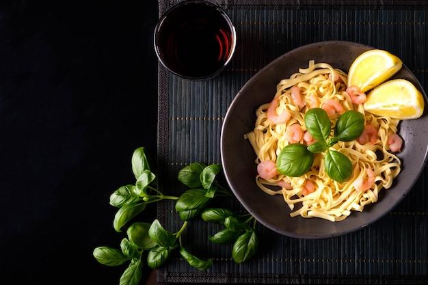 Pasta con gamberetti, basilico e pomodori su uno sfondo scuro. vista dall'alto