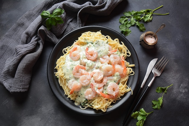 Pasta con gamberi, aglio ed erbe aromatiche in salsa cremosa alfredo