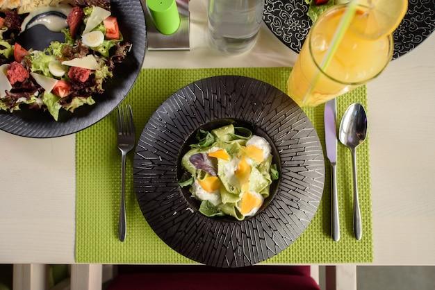 Pasta con spinaci, formaggio e basilico su un piatto nero, vista dall'alto. un bel piatto da ristorante. impostazione della tabella.