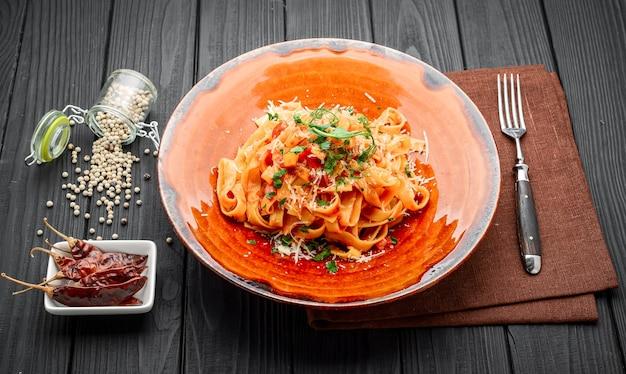 Pasta con carne di vitello, salsa di pomodoro e formaggio su un tavolo in un ristorante Foto Premium