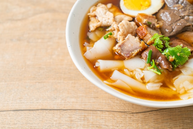 Pasta di farina di riso o quadrato di pasta cinese bollita con carne di maiale in zuppa marrone - stile alimentare asiatico