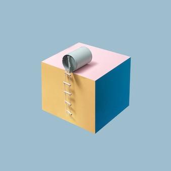 Lattina di fagioli blu pastello con scala pilota attaccata posta su un cubo rosa, blu e giallo davanti a uno sfondo blu. concetto minimalista, layout quadrato con copia spazio. astratto