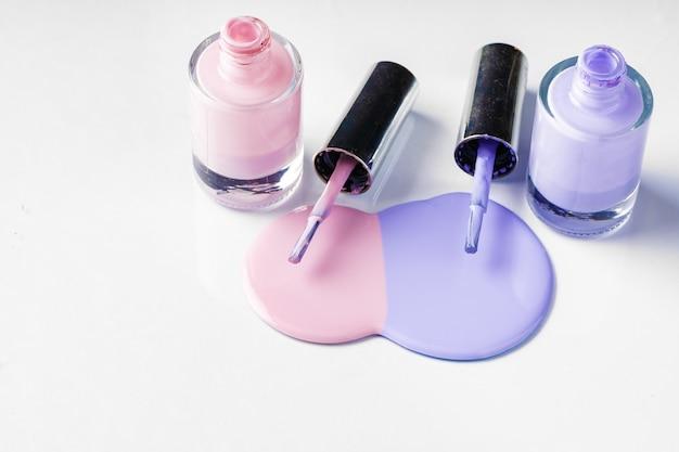 Bottiglie di smalto rovesciate di colore pastello sopra bianco