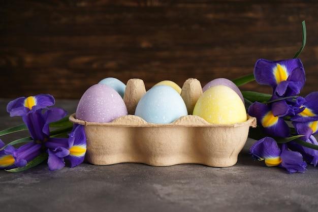 Uova di pasqua colorate pastello in una scatola di cartone e fiori freschi su uno sfondo di legno.