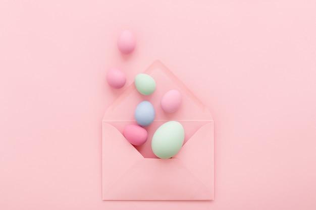 Pastello di uova di pasqua in busta rosa su sfondo rosa. lay piatto.