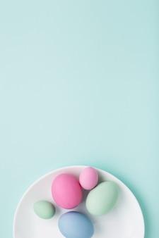 Uova di pasqua pastello su una zolla su priorità bassa blu con lo spazio della copia.