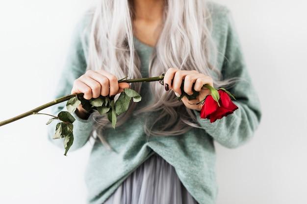 Donna gotica pastello che tiene una rosa rossa