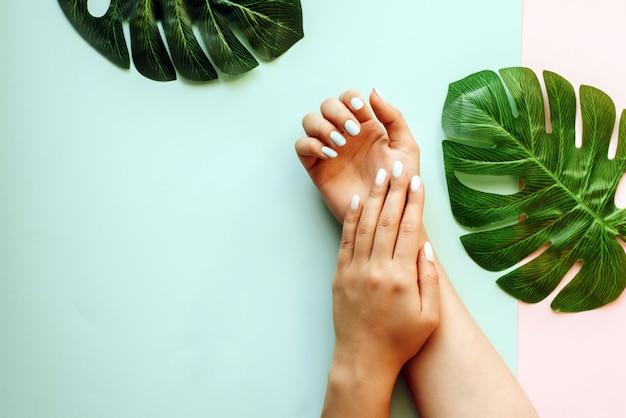 Manicure pastello su uno sfondo blu e rosa con foglie di palma. sfondo tropicale con le mani della donna