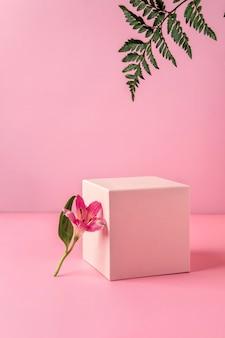 Podio rosa pastello per mostrare prodotti cosmetici con foglie di felce e fiori alstroemeria su sfondo rosa.