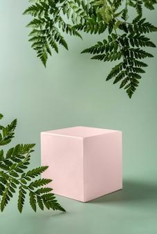 Podio rosa pastello per mostrare prodotti cosmetici con foglie di felce su sfondo verde. natura morta moderna.