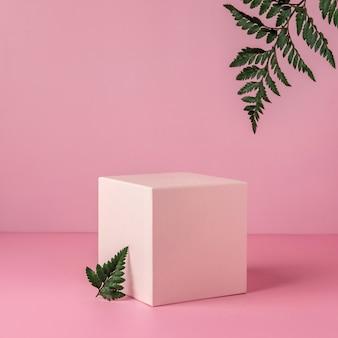Podio rosa pastello per mostrare prodotti cosmetici con foglie di felce su sfondo rosa.