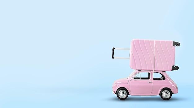 Pastello rosa retrò macchinina con grande valigia rosa su sfondo azzurro. concetto di viaggio creativo.