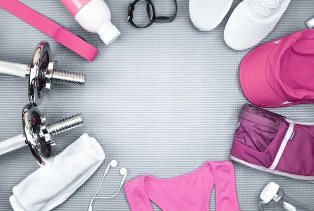 Pastello rosa e bianco attrezzature per il fitness impostato su sfondo grigio scuro del bordo di yoga