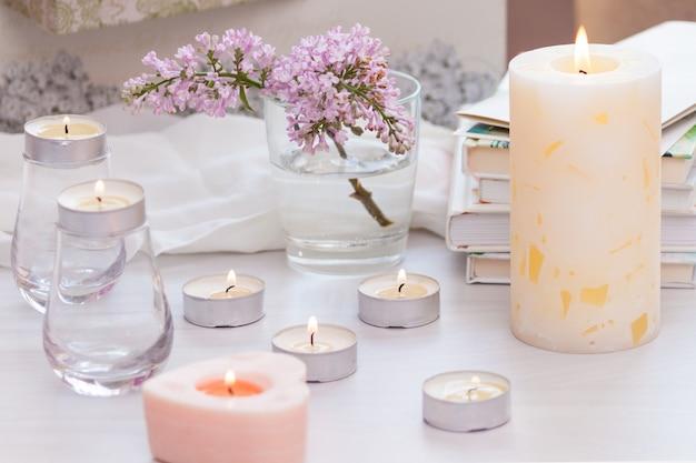 Decorazioni per interni in camera pastello con candela accesa fatta a mano, libri, fiori. concetto accogliente e rilassante.