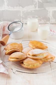 Pasties con ricotta e zucchero a velo su uno sfondo di legno chiaro pasticceria tradizionale russa sochnik