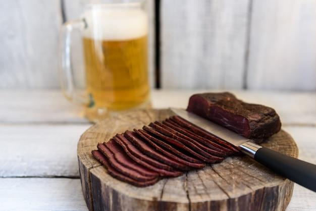 Birra pastrami in un coltello di vetro su un tavolo di legno