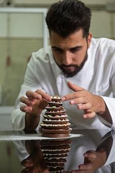 Pasticcere che rifinisce un albero di natale di cioccolato.