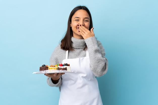 Pasticcere che tiene una grande torta sopra la parete blu felice e sorridente che copre la bocca con la mano