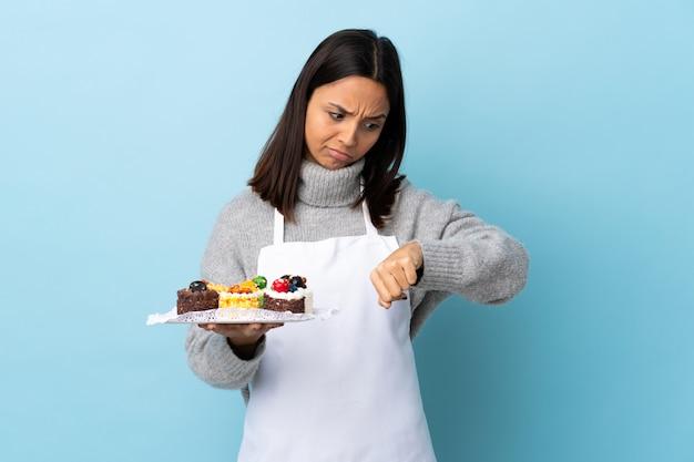 Pasticcere che tiene una grande torta sopra la parete blu che fa il gesto di essere in ritardo