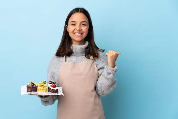Pasticcere che tiene una grande torta sopra fondo blu isolato che indica al lato per presentare un prodotto.