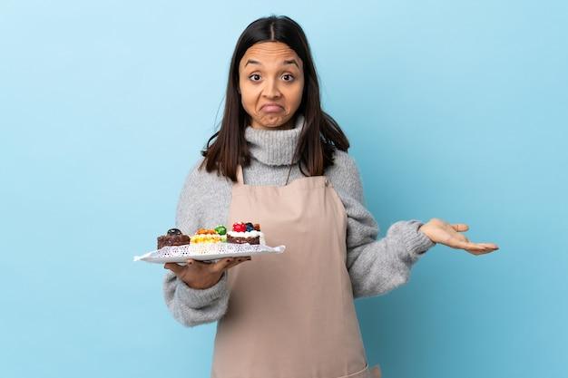 Pasticcere che tiene una grande torta sopra il blu isolato che ha dubbi mentre solleva le mani.