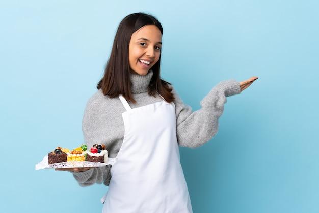 Pasticcere che tiene una grande torta sopra la parete blu isolata che estende le mani a lato per invitare a venire.