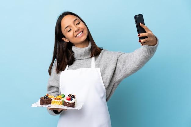 Cuoco unico di pasticceria che tiene una grande torta sopra la parete blu isolata che fa un selfie