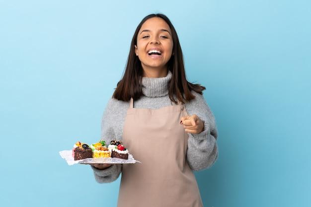 Pasticcere che tiene una grande torta sopra la parete blu isolata sorpreso e che indica la parte anteriore.