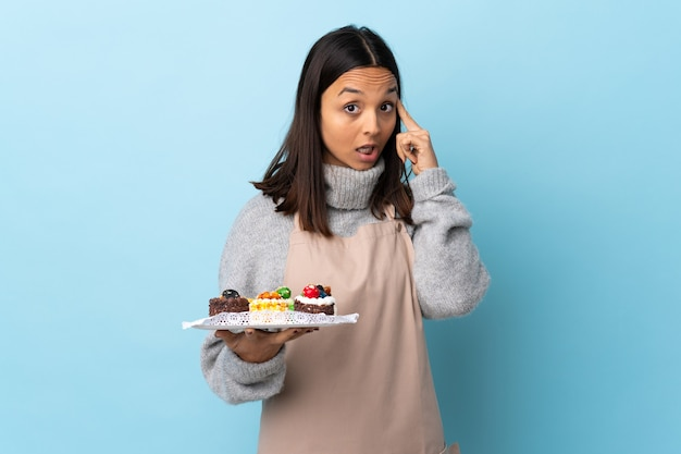 Pasticcere che tiene una grande torta sopra la parete blu isolata che pensa un'idea.