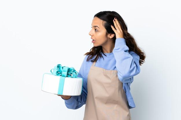 Pasticcere che tiene una grande torta sopra bianco isolato che ascolta qualcosa mettendo la mano sull'orecchio