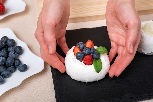 Il pasticcere prepara una torta delicata con frutti di bosco e menta