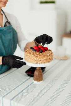 Pasticcere che prepara torta di miele decorata con cibo dolce primo piano frutti di bosco