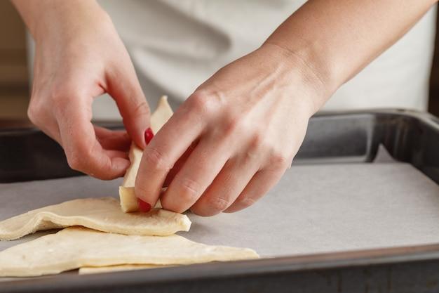 Il pasticcere modella l'impasto con le mani per i biscotti
