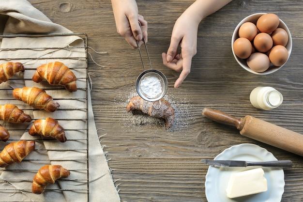 Pasticcere guarnendo un cornetto fresco fatto a mano con zucchero a velo