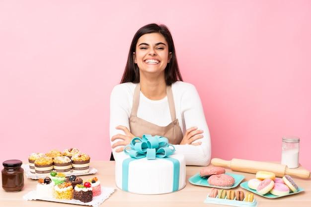 Pasticcere con una grande torta in un tavolo sopra il rosa isolato mantenendo le braccia incrociate in posizione frontale